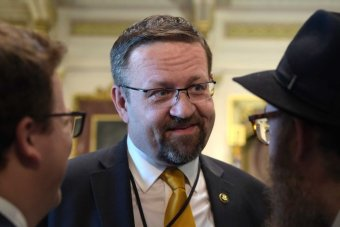 A close-up of Sebastian Gorka wearing a suit smilies while talking to two men either side of him